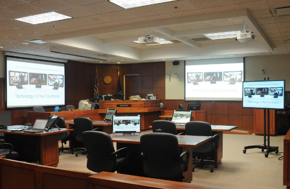 Image shows courtroom with screens for info to be shown.